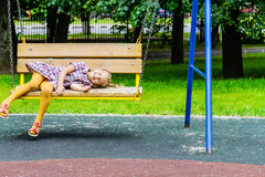 Portrait of a little blond girl on swing Royalty Free Stock Image