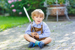 Portrait of little blond kid boy with toy sword Royalty Free Stock Photography