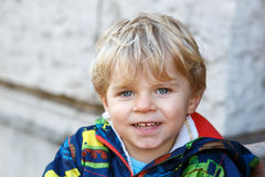 Portrait of little blond toddler boy smiling outdoors Royalty Free Stock Images