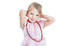 Portrait of little blonde girl. Putting on red beads Royalty Free Stock Photos