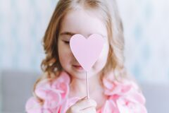 Portrait of little blonde girl holding pink wooden heart in front of her face with her eyes closed.