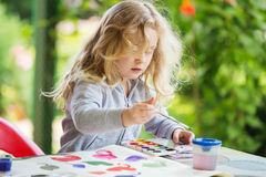 Portrait of little blonde girl painting, summer outdoor Royalty Free Stock Photography