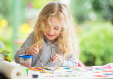 Portrait of little blonde girl painting, summer outdoor Stock Image