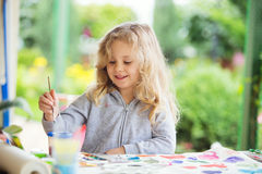 Portrait of little blonde girl painting, summer outdoor Stock Photo