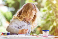 Portrait of little blonde girl painting, summer outdoor. Stock Photos