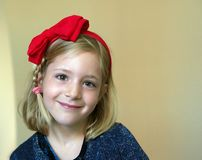Portrait of a little blonde girl with a red bow on his head Stock Photos