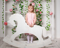 Portrait of a little blonde girl  standing near the wooden horse Royalty Free Stock Image