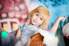 Portrait of little blonde sad girl playing with toy candy. Christmas and New Year theme royalty free stock photography