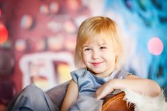 Portrait of little blonde sad girl playing with toy candy. Christmas and New Year theme royalty free stock photo