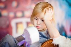 Portrait of little blonde sad girl playing with toy candy. Christmas and New Year theme royalty free stock photos