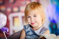 Portrait of little blonde smiling girl playing with toy candy. Christmas and New Year theme royalty free stock images