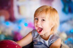 Portrait of little blonde smiling girl playing with toy candy. Christmas and New Year theme stock photo