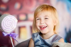 Portrait of little blonde smiling girl playing with toy candy. Christmas and New Year theme stock photography