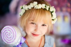 Portrait of little blonde smiling girl with toy candy and white flower diadem. Christmas and New Year theme royalty free stock photos