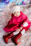 Portrait of little blonde smiling girl wears white beret, red boots, pink cloak and plays with toy candy. Christmas and New Year royalty free stock image