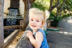 Close up Portrait of little blondy toddler Girl Smiling at Camera. Happy kid walking outdoors in the park or zoo. Family recreatio stock photo
