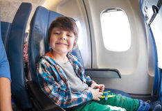 Portrait of little boy in airplane seat by window Stock Image