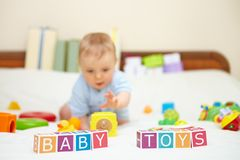 Portrait of little boy on bed. Baby toys concept. Stock Image
