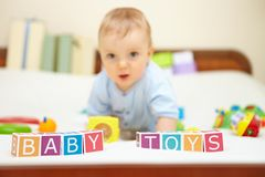Portrait of little boy on bed. Baby toys concept. Royalty Free Stock Photo