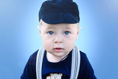Portrait of a little boy with blue eyes. On a blue background Stock Photo