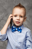 Portrait of little boy in blue shirt and bow tie with mobile pho Stock Photography