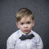 Portrait of a little boy with bowtie. Two year old boy looking straight into the camera wearing a grey bowtie Stock Photo