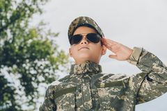 Portrait of little boy in camouflage clothing and sunglasses saluting with cloudy sky. On backdrop stock photos