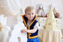 Portrait of little boy in a carnival costume on a toy horse Royalty Free Stock Images