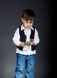 Portrait of little boy counting money. On dark background Stock Photo