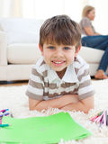 Portrait of little boy drawing lying on the floor. In the living room Stock Photography