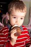 Portrait of a little boy eating tasty cocoa muffin with whipped topping Stock Images
