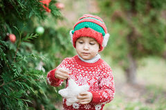 Portrait of a little boy in elf hat and red sweater near the christmas tree and holding decoration Royalty Free Stock Images