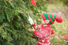 Portrait of a little boy in elf hat and red sweater near the christmas tree and holding decoration Royalty Free Stock Photo
