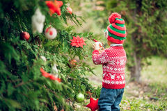 Portrait of a little boy in elf hat and red sweater near the christmas tree and holding decoration Royalty Free Stock Photos