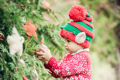 Portrait of a little boy in elf hat and red sweater near the christmas tree and holding decoration. Half-length portrait of a little boy in elf hat and red Royalty Free Stock Photo
