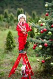 Portrait of a little boy in elf hat and red sweater near the christmas tree and holding decoration Royalty Free Stock Image