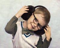 Portrait of a little boy in fur headphones stock image