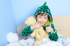 Portrait of little boy gesturing thumbs up with teddy bear in bed Stock Images