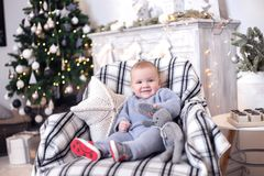 Portrait of a little boy with a gift. New Year`s holidays. Sitting on sofa Royalty Free Stock Images