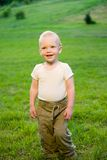 Portrait of little boy on green grass field Royalty Free Stock Photography