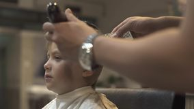 Portrait little boy while hairdressing with electrical shaver in children barbershop. Hairstylist using electrical razor. For children hairstyle. Haidresser stock video
