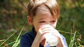 Portrait of a little boy. A happy child drinks milk or milk product from a glass. Proper and natural nutrition of. Children. Production of dairy products stock video footage