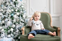 Portrait little boy. Happy new year. decorated Christmas tree. Christmas morning in bright living room. sitting on green. Chair royalty free stock images