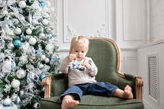 Portrait little boy. Happy new year. decorated Christmas tree. Christmas morning in bright living room. sitting on green. Chair royalty free stock image