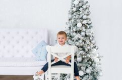 Portrait of little boy. decorated Christmas tree. Christmas day in bright living room. Sitting on white chair. Portrait of little boy. Happy new year. decorated royalty free stock photos