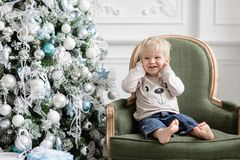 Portrait little boy. Happy new year. decorated Christmas tree. Christmas morning in bright living room. sitting on green. Chair stock images