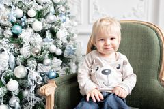 Portrait little boy. Happy new year. decorated Christmas tree. Christmas morning in bright living room. sitting on green. Chair stock photo