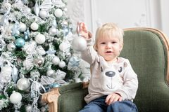 Portrait little boy. Happy new year. decorated Christmas tree. Christmas morning in bright living room. sitting on green. Chair stock photos