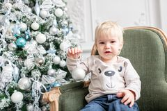 Portrait little boy. Happy new year. decorated Christmas tree. Christmas morning in bright living room. sitting on green. Chair royalty free stock photo