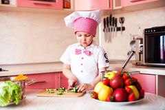 Portrait of little boy in the hat of the chef and an apron. Little cooks chef in the kitchen tasting the dish. Royalty Free Stock Images